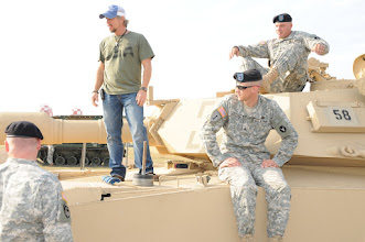 Photo: Veteran Cody James talks with soldiers about an M1 Abrams Tank.