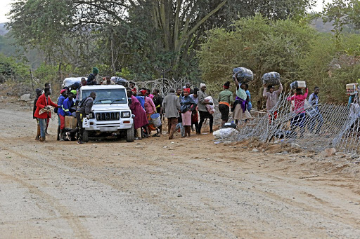 Zimbabweans who crossed illegally into SA to shop for groceries cross back into their country through one of the many gaps in the R40m Beitbridge border fence.