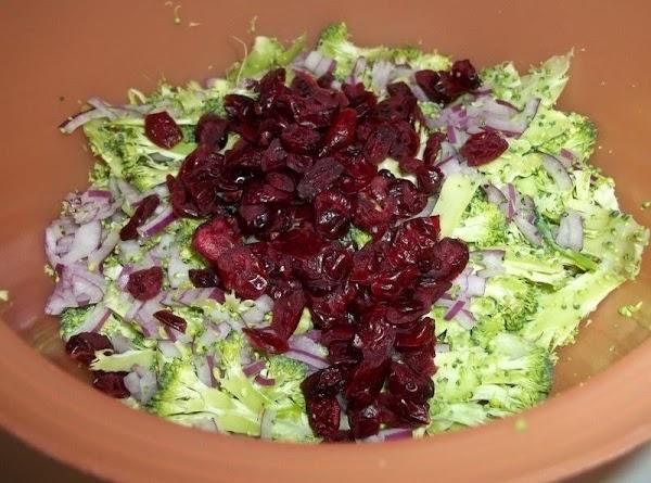 In a bowl, toss the broccoli, carrots, raisins, onions, cranberries.