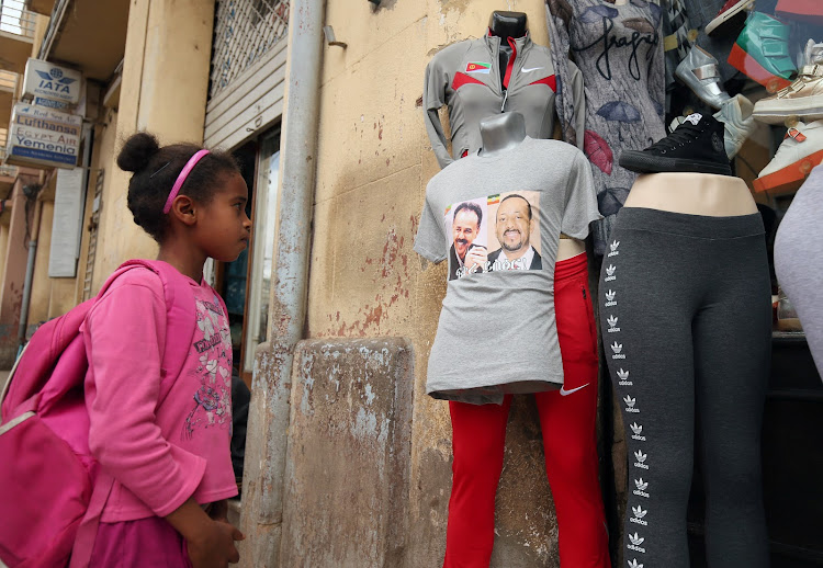 A girl looks at a T-shirt with a pictures of Eritrea's president Isaias Afwerki and Ethiopia's prime minister Abiy Ahmed dressed on a mannequin for sale in Asmara, Eritrea on July 20 2018.
