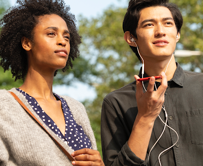 A man and a woman standing next to each other outside. The man is holding a mobile device and listening to headphones.