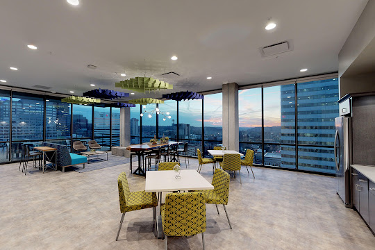 Community clubhouse with a kitchen, lounge areas, and beautiful city views
