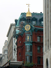 Photo: A colorful and ornate brick and copper-accented building from the 19th century with a gilded clockface, dome, and weathervane.