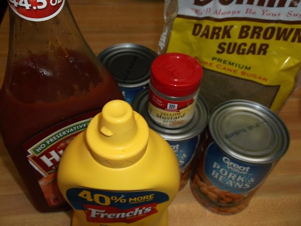 In a 2 quart baking dish, mix together the ketchup, yellow mustard, dark brown...