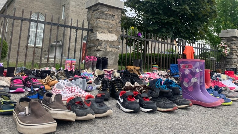 childrens' shoes are placed in front of a church in memory of the 215 children.