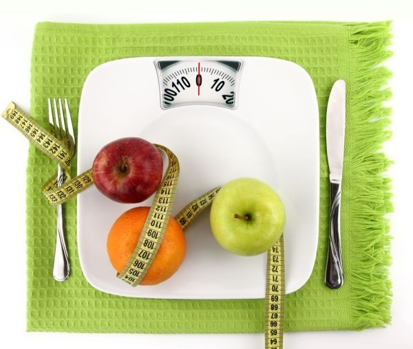 Stock image of a scale, fruit, tape measure and utensils.
