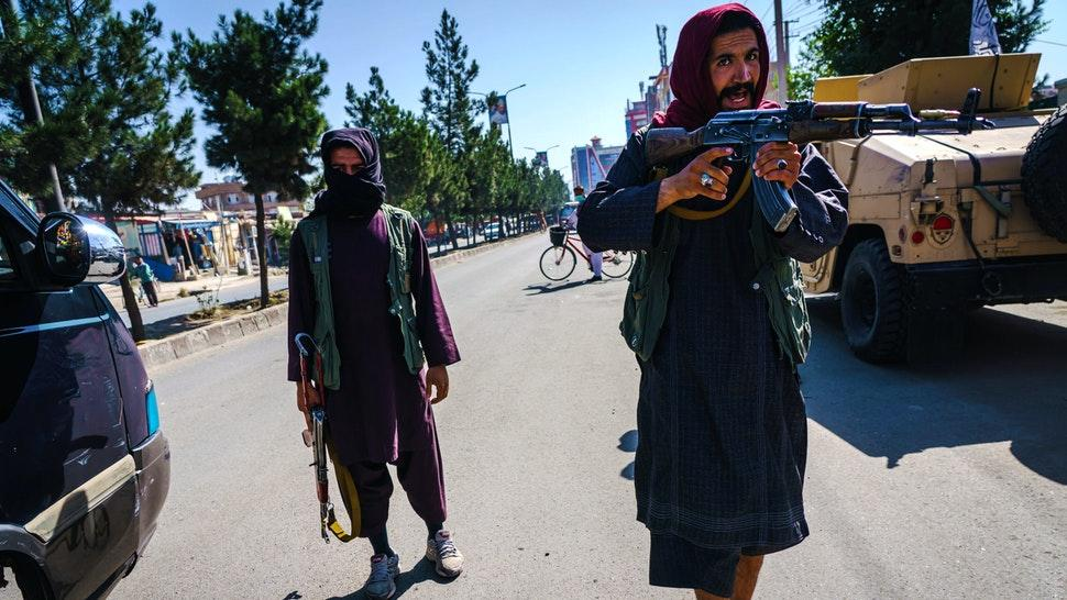 KABUL, AFGHANISTAN -- SEPTEMBER 8, 2021: Taliban fighters try to stop the advance of protesters marching through the Dashti-E-Barchi neighborhood, a day after the Taliban announced their new all-male interim government with a no representation for women and ethnic minority groups, in Kabul, Afghanistan, Wednesday, Sept. 8, 2021.