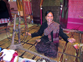 Photo: Another Phu Thai woman in traditional dress spins silk threads at the demonstration in JJ Mall.