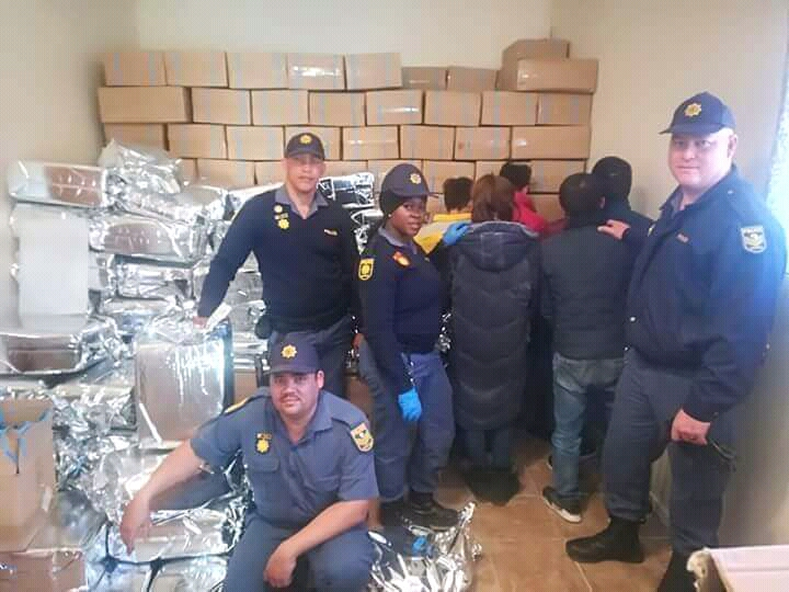 Members of the SAPS in the Northern Cape and the arrested suspects who are accused of allegedly selling counterfeit goods in Hartswater on July 17 2018
