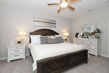 Model bedroom with light carpet, ceiling fan, and bed with wooden headboard and white bedding