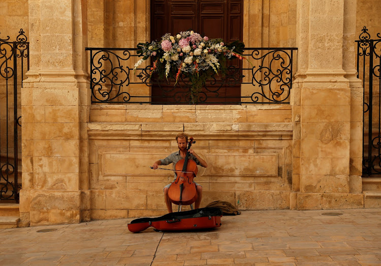 A street musician plays the cello in front of Saint Catherine's Church in Valletta.