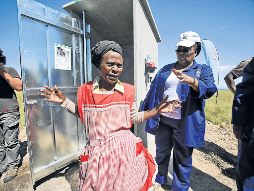 FLUSHED: Nozipho Ntintili from California village near Ngqamakwe receives her new toilet from ADM Mayor Nomasikizi Konza at the official launch of the R631-million toilet programme, which has since stalled and become mired in controversy Picture: MARK ANDREWS