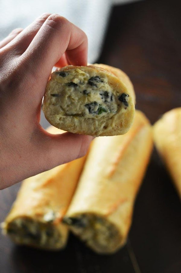 Stuff the hollow baguette pieces with the spinach artichoke dip, using a spoon to...
