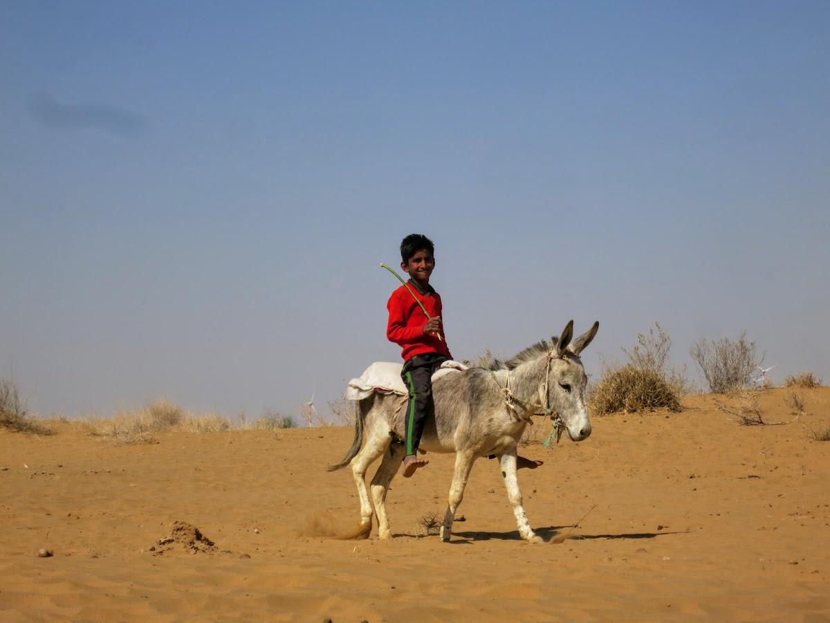 India. Rajasthan Thar Desert Camel Trek. Kid riding his donkey