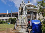 An orientation monitor sits next to the defaced statue of King George V following disruptions at UKZN's Howard College on Monday