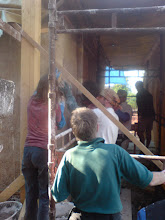 Photo: applying the final coat (throw on to maximise bonding with second layer) then rub in and smooth with single length (aluminium) edge scraping against top and bottom plaster edge timber simultaneously