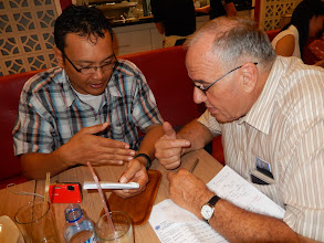 Photo: Back in Medan Pastor Richardand I going overthe finalfinancial mattersof the MTM conference expenses.