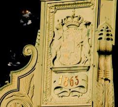 Photo: Eisengussdenkmal zur Erinnerung an die Befreiungskriege aus dem Jahre 1863 mit den Wappentieren Mecklenburgs.  A: Herzogtum Mecklenburg: Auf goldenem Grunde ein schwarzer Stierkopf mit aufgerissenem roten Maule und ausgestreckter roter Zunge; auf dem Kopfe silberne Hörner und eine goldene Lilienkrone. B: Herrschaft Rostock: Auf blauem Grunde schreitend ein goldener Greif mit ausgestreckter Zunge und aufgehobener rechter Vorderklaue.
