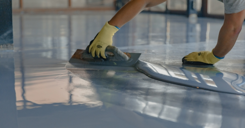 a person applies epoxy to a garage floor