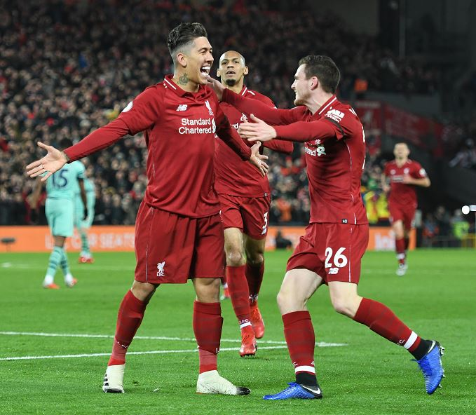 Liverpool's Roberto Firmino scores the first goal and celebrates during the Premier League match against Arsenal FC at Anfield on Saturday.