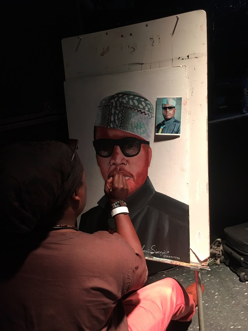 Celebrity funeral artist Lebani Sirenje aka Rasta working on a painting of the late rapper