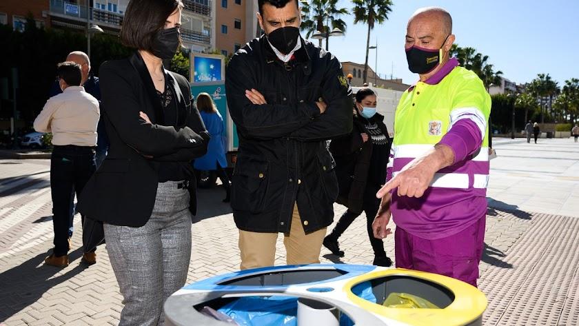 Representantes del Ayuntamiento y un trabajador observan una de las nuevas papeleras