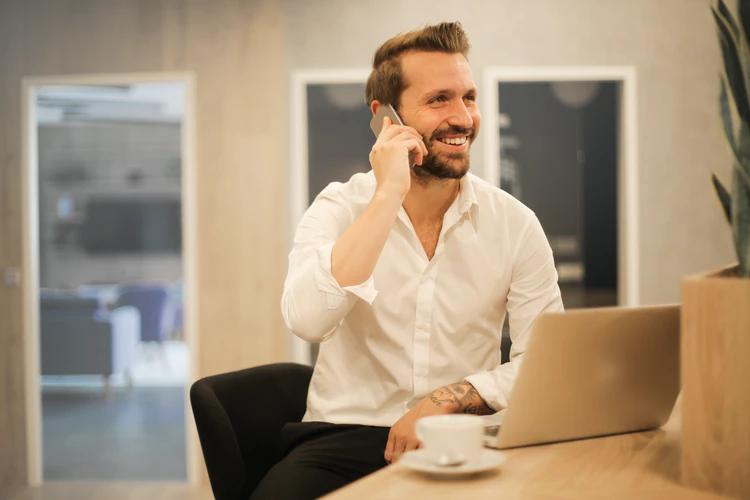 Empreender com Protheus e Power BI: homem sentado sorrindo com o celular na orelha