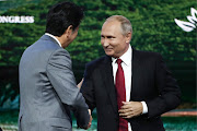 Japanese Prime Minister Shinzo Abe shakes hands with Russian President Vladimir Putin during a session of the Eastern Economic Forum in Vladivostok, Russia, on September 12, 2018.