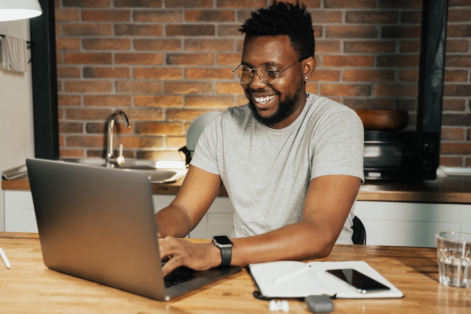 jeune homme souriant devant son ordinateur