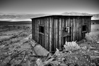Photo: Lagos' Lodge  This is a shot of +Ricardo Lagosfrom our trip to Death Valley this past winter. Ricardo was kind enough to put his camera down for a few seconds and peek out from this shack for a couple shots. In honor of him I put this into B/W which I think highlights the textures of the shack and landscapes well.  This shack sits at an abandoned mine at the end of a road that truly tested our rental car. We made it most of the way before having to hoof it the rest. It's fun to get out and explore some of these lesser known places and to wonder what life was like for those that worked here.  #blog