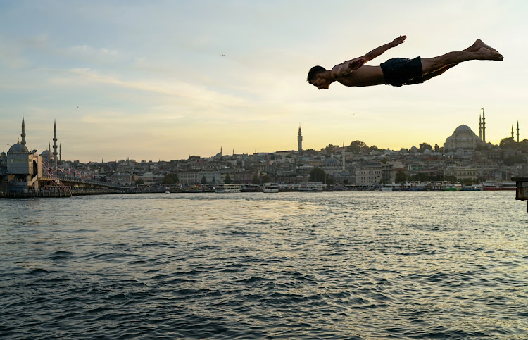 A boy jumps into the sea at Karakoy district in Istanbul, Turkey.