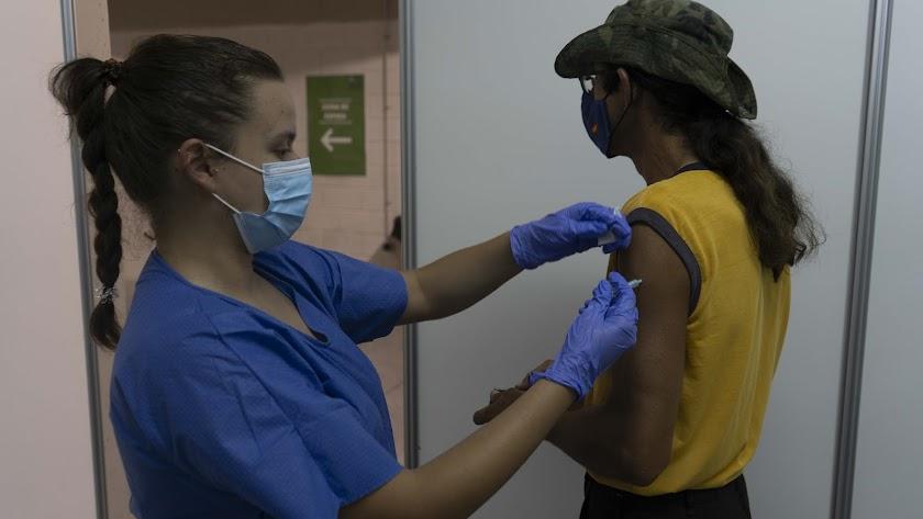Una enfermera vacuna a una joven en Almería.