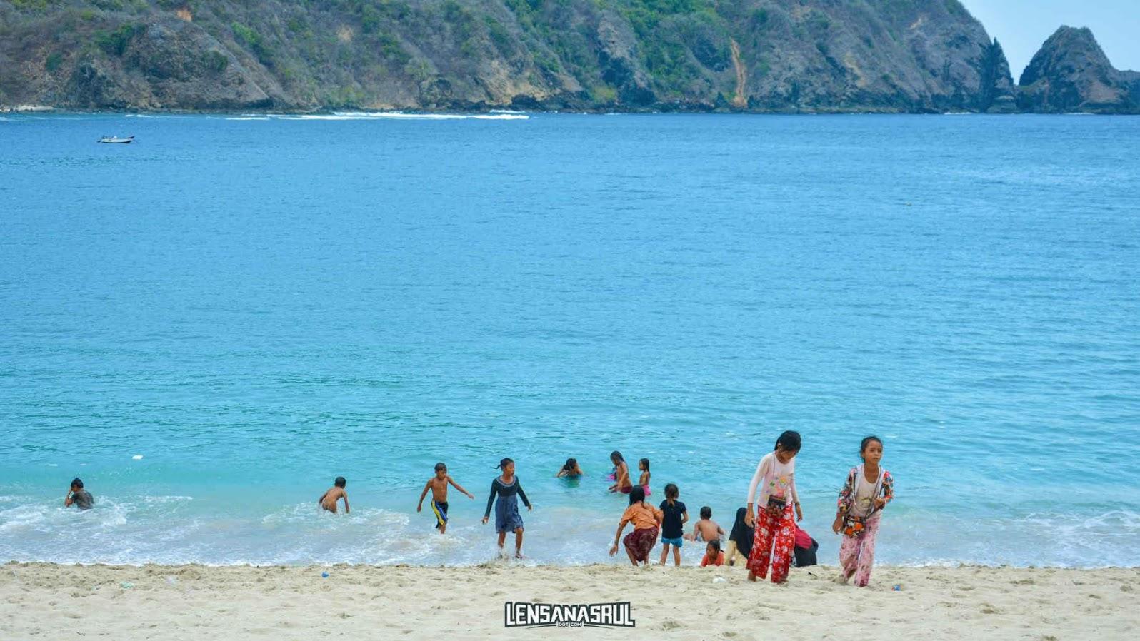 anak anak bermain air di pantai mawun