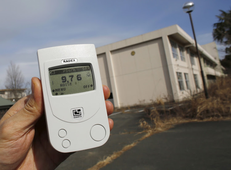 A Reuters reporter measures a radiation level of 9.76 microsieverts per hour in front of Kumamachi Elementary School inside the exclusion zone in Okuma, near Tokyo Electric Power Co's (TEPCO) tsunami-crippled Fukushima Daiichi nuclear power plant, Fukushima Prefecture, Japan, February 13, 2016.
