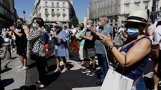 Transeúntes aplauden al finalizar el minuto de silencio en memoria por los fallecidos por el COVID-19 en Madrid.