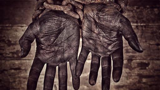 Representación de la esclavitud con unas manos sucias encadenadas
