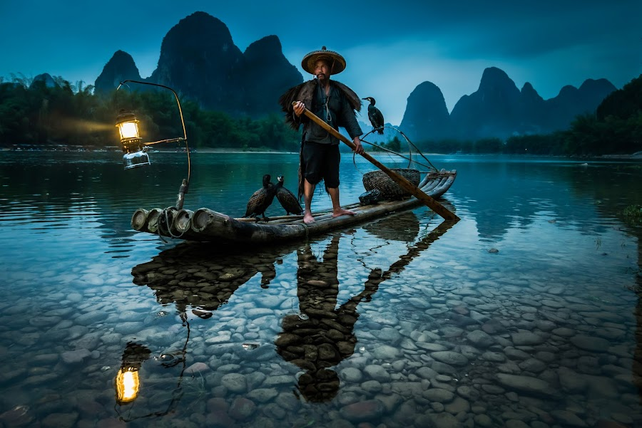 Warrior by Andy Beales - People Street & Candids ( environmental portrait, china travel, blue hour, li river, guilin fishermen, guilin china, travel, people, guangxi, bamboo raft, li, cormorant fishing, asia, lamp, cormorant fisherman, raft, guilin, travel photography,  )