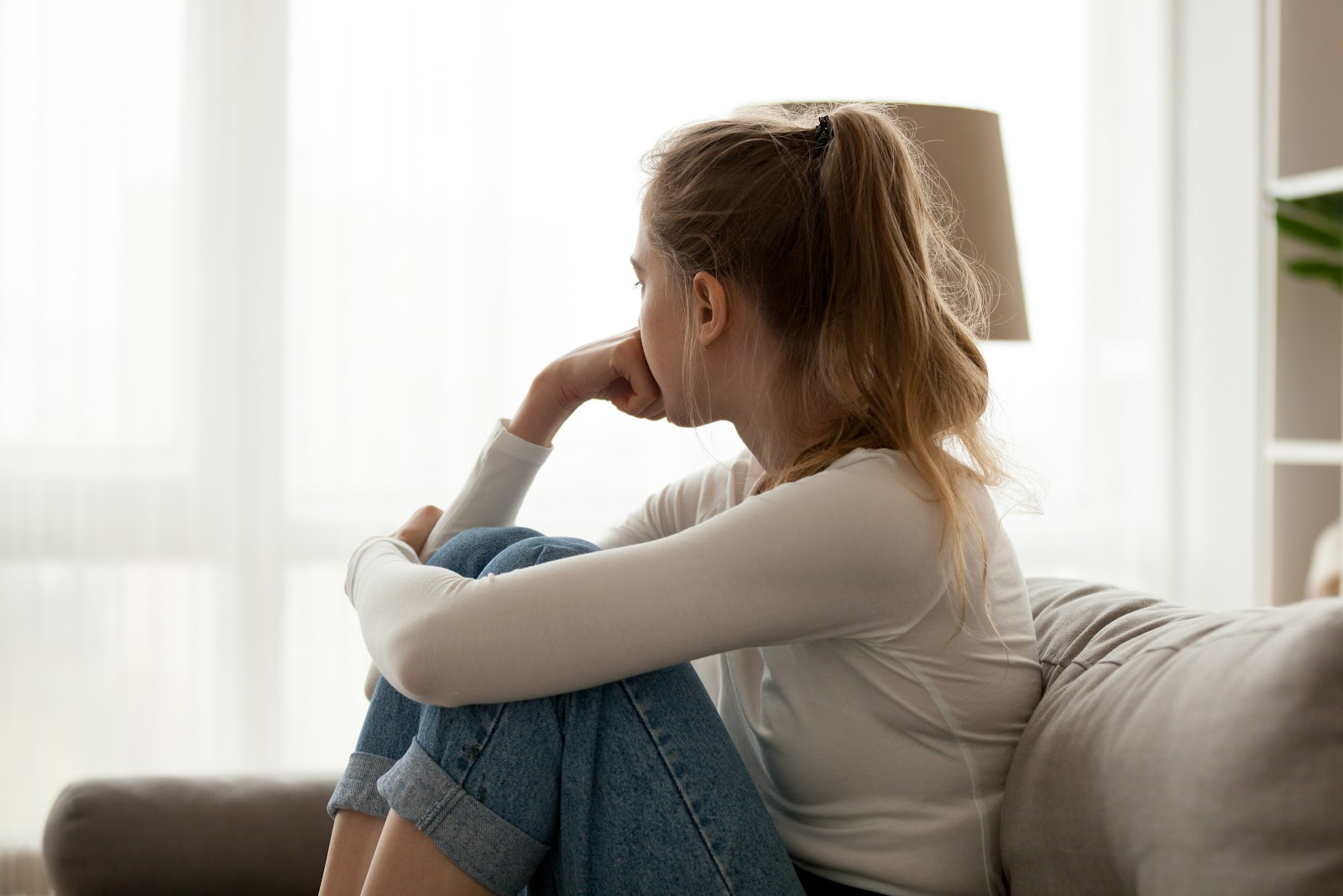 A lonely woman looking out a window while sitting on the couch