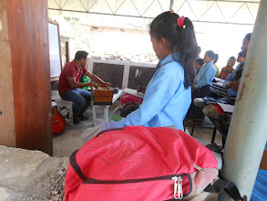 Photo: The teacher teaching the children to play the harmonium