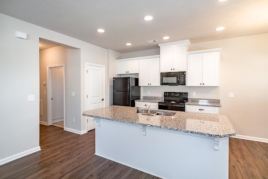 Kitchen with white cabinets, black appliances, and granite countertops