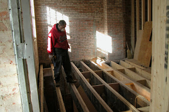 Photo: February 2005 - Month 18: Kitchen getting new floor joists. Leo on the balance beams.
