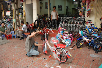 Photo: Though there are more and more cars and scooters on the street, bicycles are still very popular in Hanoi. Growing up kids love having a bicycle as a present. In the photo, my niece's having her first bicycle assembled.