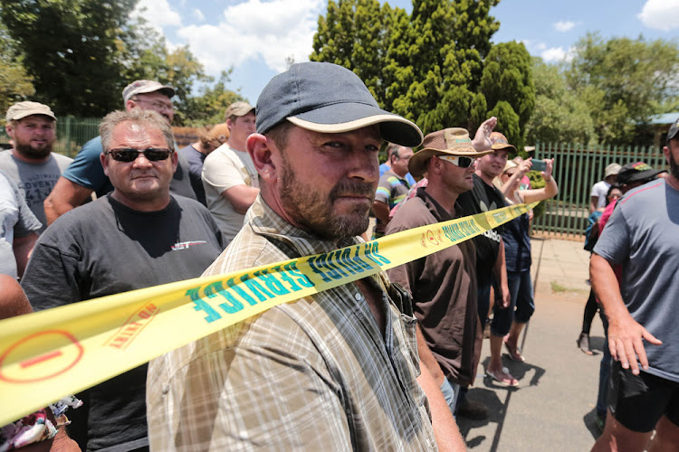 Members of the farming community gather to watch protesters during demonstrations outside Hoerskool Overvaal in Vereeniging on the second day of protests there.
