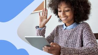 una niña mirando un tablet y levantando la mano