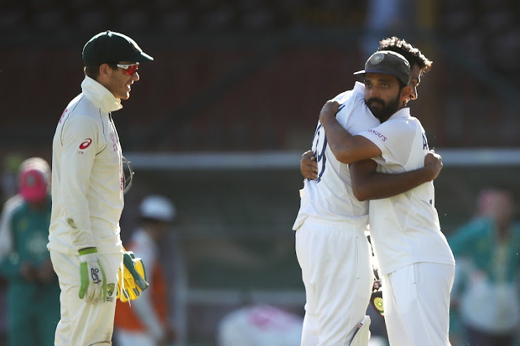 Tim Paine of Australia watches on as Ravichandran Ashwin of India embraces his captain Ajinkya Rahane of India as they celebrate securing a draw during day five of the Third Test match in the series between Australia and India at Sydney Cricket Ground on January 11, 2021 in Sydney, Australia.