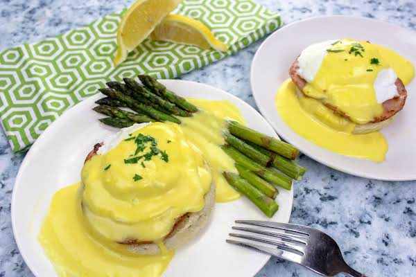 Classic Hollandaise Drizzled Over Poached Eggs And Asparagus.