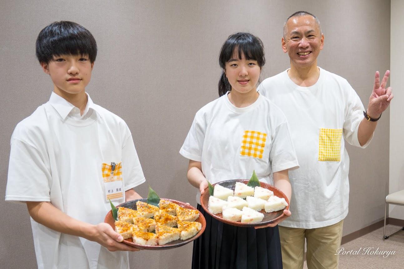 優勝作品「おむすび」を手にする村上さん、金打さん、谷垣会長と一緒に