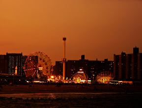 """Photo: """"City of candles...""""  Coney Island is the site of my favorite New York City beach. The Rockaways in Queens have become popular over the last few years and while I have fond memories of the Rockaways (since I grew up in Queens) Coney Island tugs at my heart in the best way possible. There is nothing like standing on the old pier that juts out into the Atlantic ocean while watching the waves crash onto the shore as the lights on the Wonder Wheel and the Cyclone twinkle in the distance like a tiny city of candles.  When I was much younger, I moved to New Mexico for a year and a half. I was in high school at the time and many fellow students would ask me what it was like to live so close to the ocean and I could never quite explain what it was like at the time. I was always at a loss for words. It was what I grew up with and it was hard for me to imagine life without access to the ocean.  Years later, it's still hard to fully put into words what it is like: breathing in salty ocean air, viewing the night sky while listening to waves, the feel of cool sand on bare feet, jumping through the ocean with wild abandon.  I think I keep taking photos in an attempt to further explain what the ocean means to me. Isn't that why we write, take photos, paint, dance, create music and engage in a variety of other artistic pursuits? It's to put into form those feelings and experiences that remain otherwise formless.    New York Photography: The Wonder Wheel and Cyclone at Coney Island, Brooklyn.    You can view this post along with information about purchasing prints of this image if you wish at my site here:  http://nythroughthelens.com/post/24704765445/coney-island-beach-at-sunset-with-the-wonder-wheel  -  Tags: #photography  #newyorkcity  #newyorkcityphotography  #brooklyn  #coneyisland  #coneyislandbeach  #sunset  #landscape  #ocean  #writing  #prose  #wonderwheel  #cyclone"""