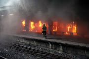 A fireman sprints along a platform at Cape Town's central railway station as a train burns. Arson attacks have reduced the size of the city's train fleet by more than half since 2015.