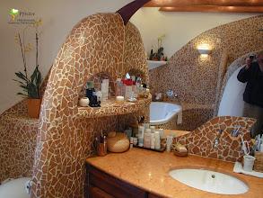 Photo: Waschtischunterbau in Zwetschgenholz mit gebogener Front und frei geformten Griffen. Die mit Mosaik belegten, runden Abmauerungen verleihen dem Badezimmer einen Höhlencharakter im Stil von dem Künstler Gaudi.